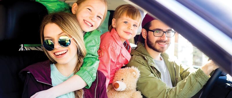 Mom and dad and 2 children in vehicle with teddy bear