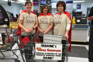 3 ladies dressed in cape behind a grocery shopping cart